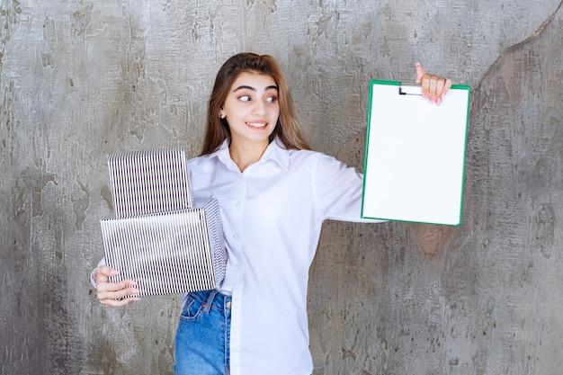 Dziewczyna w białej koszuli trzymająca srebrne pudełka na prezenty i białą listę podpisów