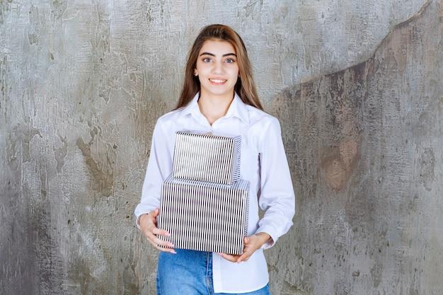Dziewczyna w białej koszuli trzymająca srebrne pudełka na prezenty