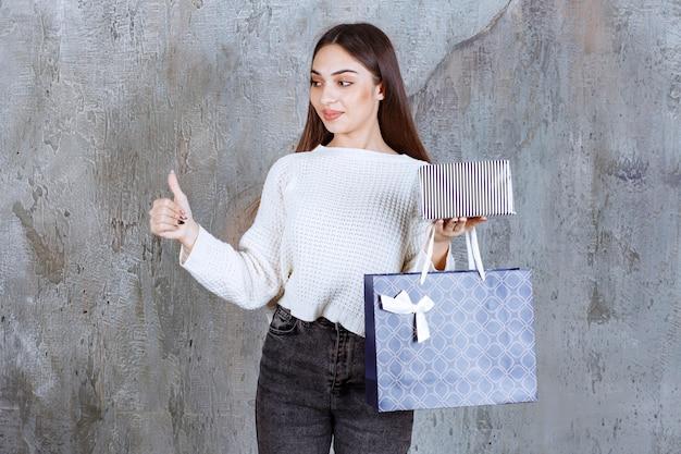 Dziewczyna w białej koszuli trzymająca srebrne pudełko i niebieską torbę na zakupy oraz pokazująca znak pozytywnej ręki.