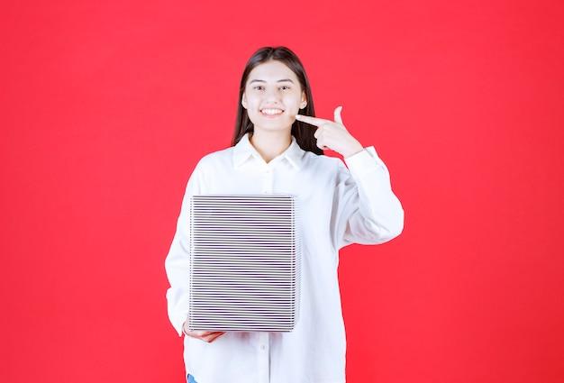 Dziewczyna w białej koszuli trzymająca srebrne pudełko upominkowe