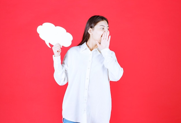 Dziewczyna w białej koszuli trzymająca tablicę informacyjną w kształcie chmury i dzwoniąca do kogoś