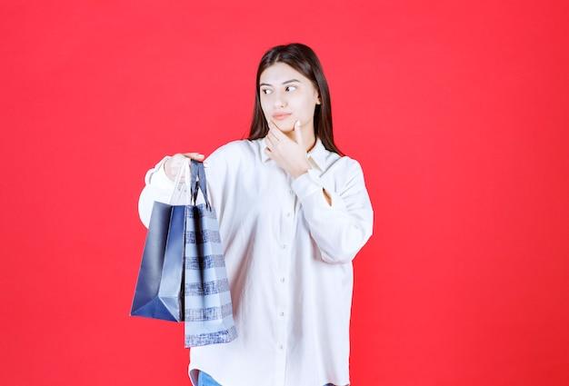 Dziewczyna w białej koszuli trzymająca wiele toreb z zakupami i wygląda na zdezorientowaną i niezdecydowaną