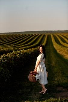 Dziewczyna w białej lekkiej sukience stoi boso na środku pola w słoneczny dzień, trzymając w rękach kosz piknikowy