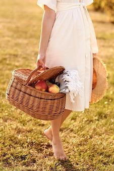 Dziewczyna w białej lekkiej sukience stojącej na środku pola w słoneczny dzień, trzymając w rękach kosz piknikowy.