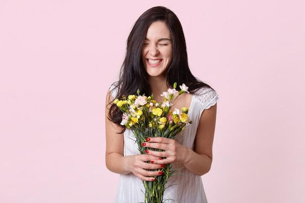 Dziewczyna w białej sukience cieszy się zapachem kwiatów i szczerze się śmieje, ciesząc się wspaniałym wiosennym dniem na różowej ścianie pozując z zamkniętymi oczami, będąc w dobrym nastroju, będąc szczęśliwą w dniu ślubu.