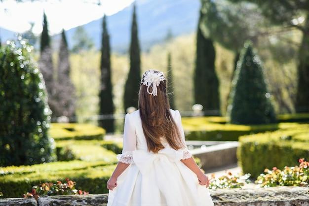 Dziewczyna w białej sukience do komunii z kokardą na plecach w parku do zdjęcia