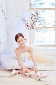 Dziewczyna w białej sukni balowej i pointe w pobliżu okna