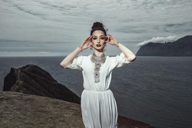 Dziewczyna w białej sukni i biżuterii stoi na klifie