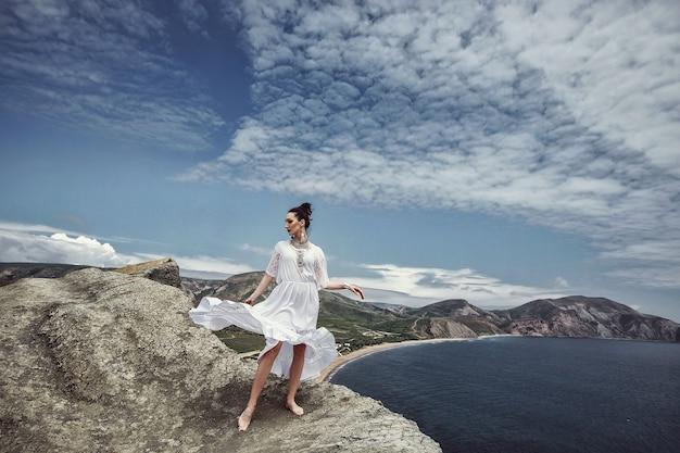 Dziewczyna w białej sukni i dekoracjach stoi na klifie