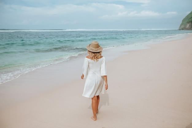 Dziewczyna w białej sukni i kapeluszu jest na białej plaży. widok z tyłu