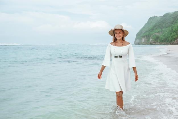 Dziewczyna w białej sukni i kapeluszu spacery po błękitnej wodzie na plaży