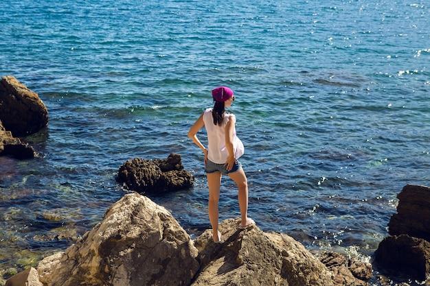 Dziewczyna w białej sukni i okularach przeciwsłonecznych nad morzem