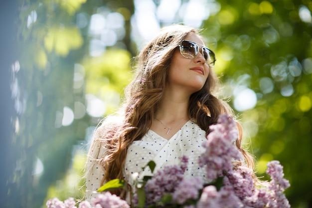 Dziewczyna w białej sukni i okularach przeciwsłonecznych trzyma w rękach wiklinowy kosz z kwiatami. kosz z bzami. dziewczyna i kwiaty. chodzenie z koszem bzu w rękach. florystyka