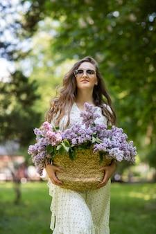 Dziewczyna w białej sukni i okularach przeciwsłonecznych trzyma w rękach wiklinowy kosz z kwiatami. kosz z bzami. dziewczyna i kwiaty. spacer z koszem bzu w rękach. florystyka. wiosenny kwiat bzu.