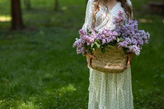 Dziewczyna w białej sukni i okularach przeciwsłonecznych trzyma w rękach wiklinowy kosz z kwiatami. kosz z bzami. dziewczyna i kwiaty. spacer z koszem bzu w rękach. florystyka
