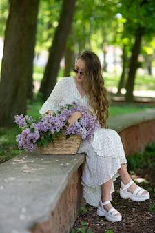 Dziewczyna w białej sukni i okularach przeciwsłonecznych trzyma w rękach wiklinowy kosz z kwiatami. kosz z bzami. dziewczyna i kwiaty. usiądź z koszem bzu w rękach. florystyka