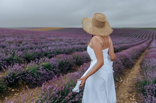 Dziewczyna w białej sukni i słomkowym kapeluszu na lawendowym polu