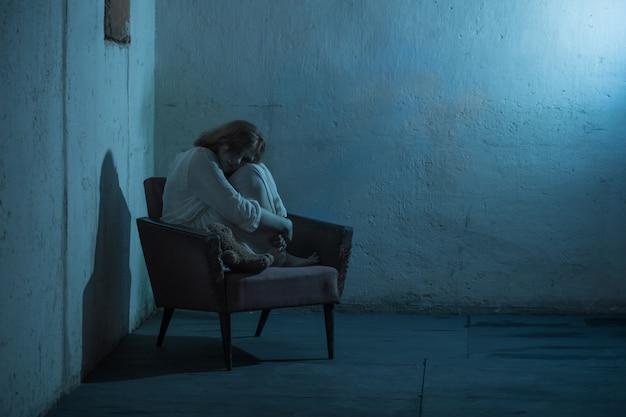Dziewczyna w białej sukni na starym fotelu w piwnicy