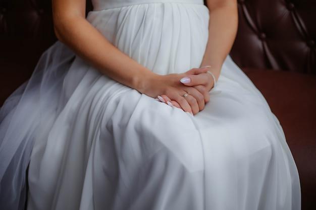 Dziewczyna w białej sukni siedzi na miękkim fotelu, trzymając ręce na kolanach. ręce panny młodej, biała sukienka, panna młoda. poranek weselny.