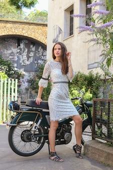 Dziewczyna w białej sukni stoi samotnie przy motocyklu w paryżu