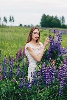 Dziewczyna w białej sukni stoi wśród łubinów