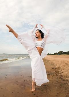 Dziewczyna w białej sukni tańczy nad brzegiem morza
