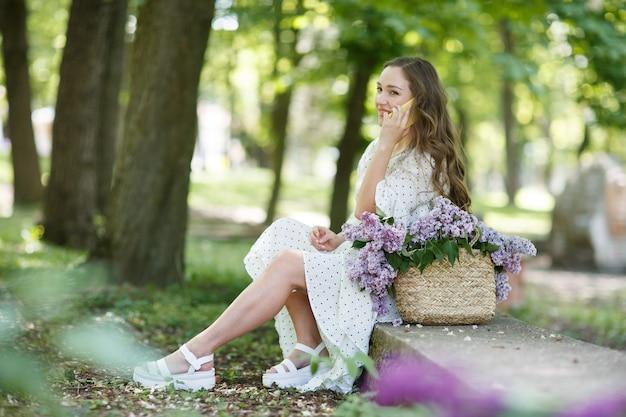 Dziewczyna w białej sukni trzyma w rękach wiklinowy kosz z kwiatami i telefonem. kosz z bzami. dziewczyna i kwiaty. usiądź z koszem bzu w rękach. florystyka
