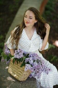 Dziewczyna w białej sukni trzyma w rękach wiklinowy kosz z kwiatami. kosz z bzami. dziewczyna i kwiaty. usiądź z koszem bzu w rękach. florystyka