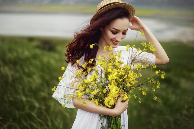 Dziewczyna w białej sukni, w eleganckim kapeluszu z bukietem żółtych polnych kwiatów