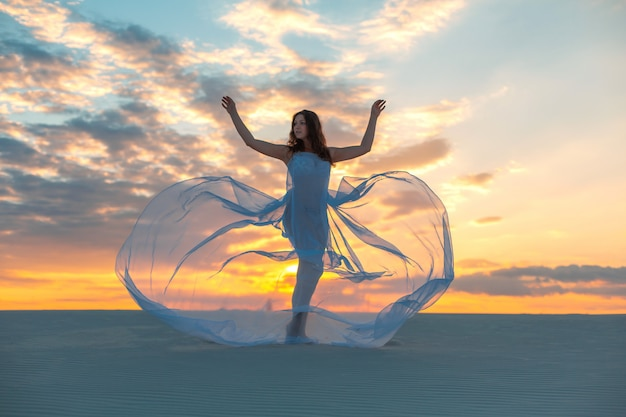 Dziewczyna w białej sukni w locie tańczy i pozuje na piaszczystej pustyni o zachodzie słońca