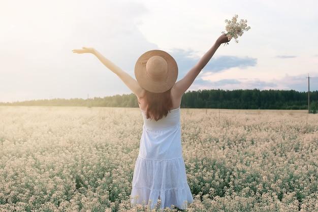 Dziewczyna w białej sukni w polu kwitnących żółtych kwiatów