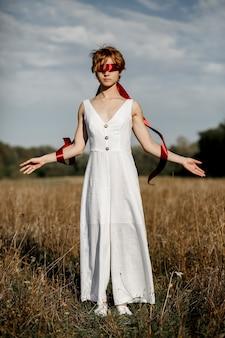 Dziewczyna w białej sukni z czerwoną wstążką