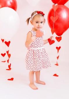 Dziewczyna w białej sukni z sercami, jedzenie lizaka w kształcie serca. dziecko trzyma czerwono-białe kulki na walentynki