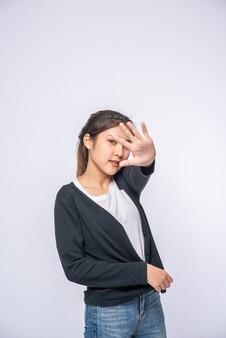 Dziewczyna w białych dżinsach ze stretchem i ręką znak zakazu na białej ścianie.