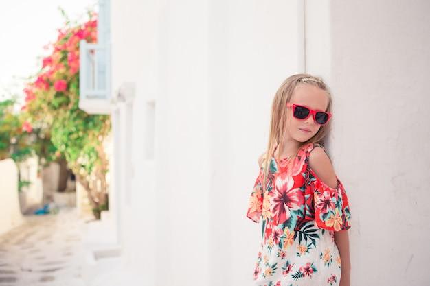 Dziewczyna w białych sukniach zabawy na świeżym powietrzu na ulicach mykonos