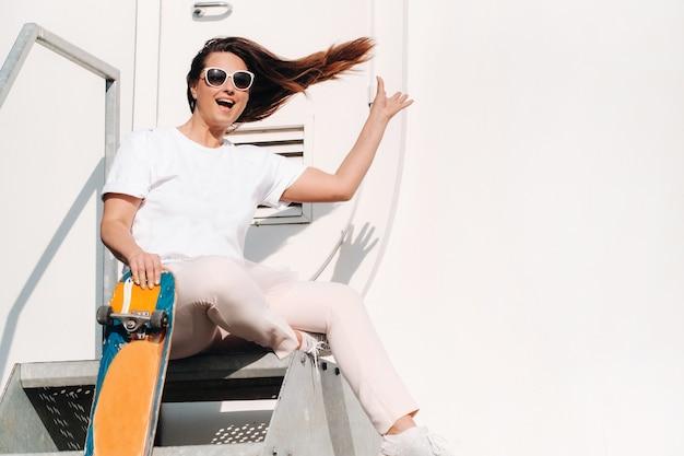 Dziewczyna w białych ubraniach i okularach ze skate w dłoniach jest fotografowana w pobliżu dużych turbin wiatrowych na polu z drzewami.