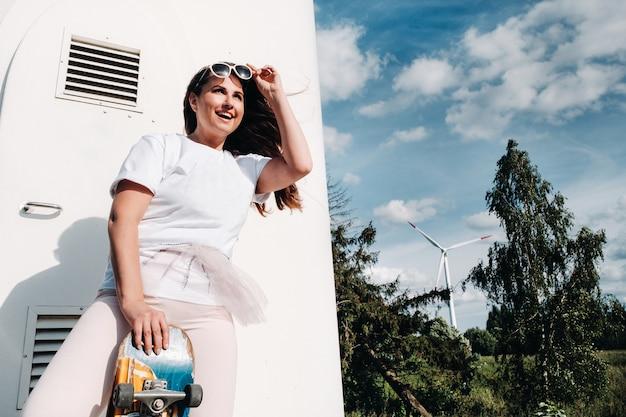 Dziewczyna w białych ubraniach i okularach ze skate w dłoniach jest sfotografowana w pobliżu dużych turbin wiatrowych na polu z drzewami. nowoczesna kobieta z deską jeździecką w polu z wiatrakami.