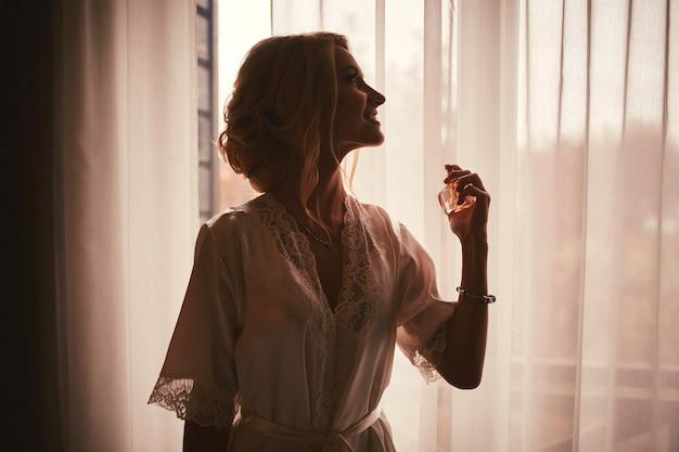 Dziewczyna w białym atłasowym szlafroku z dekoltem i francuskim manicure trzyma buteleczkę z perfumami