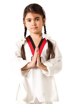 Dziewczyna w białym kimonie i akcesoriach w postaci stokrotek na warkoczykach brunetki