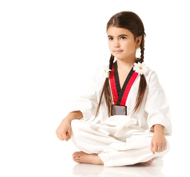 Dziewczyna w białym kimono siedzi w pozie jogi