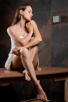 Dziewczyna w białym ręczniku siedzi na stole do masażu po zabiegach spa. na masażystę czeka profesjonalna modelka w gabinecie masażu.