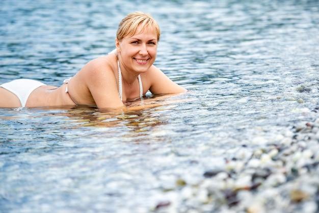 Dziewczyna w białym stroju kąpielowym leży w morzu i uśmiecha się. dziewczyna leży w wodzie i śmieje się. turcja,