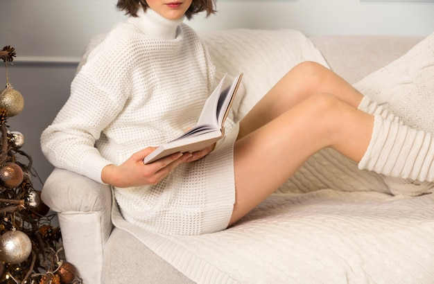 Dziewczyna w białym swetrze i leginsach siedzi na kanapie i czyta książkę