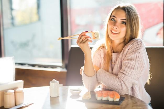 Dziewczyna w białym swetrze je sushi na obiad przy małej kawiarni