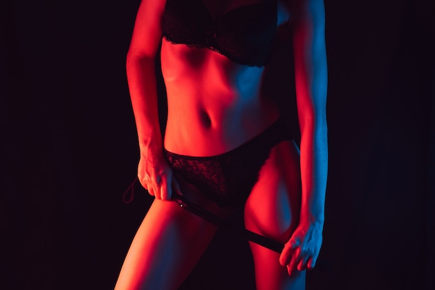Dziewczyna w bieliźnie o pięknej szczupłej sylwetce ze skórzanym batem w dłoni do erotycznych gier bdsm