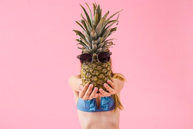 Dziewczyna w bikini pokazuje ananasa