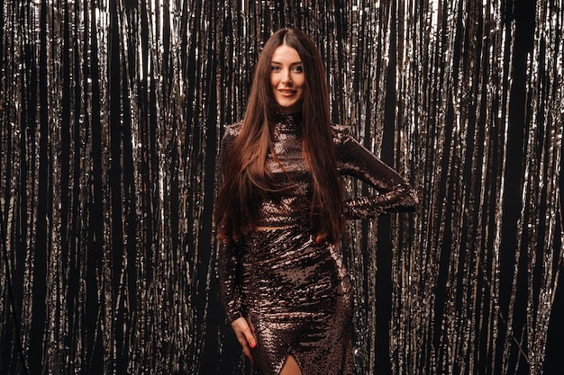 Dziewczyna w błyszczącej sukience na srebrnym tle noworocznego deszczu.