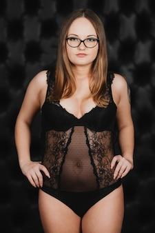 Dziewczyna w body z czarnej koronki i pozowanie okulary