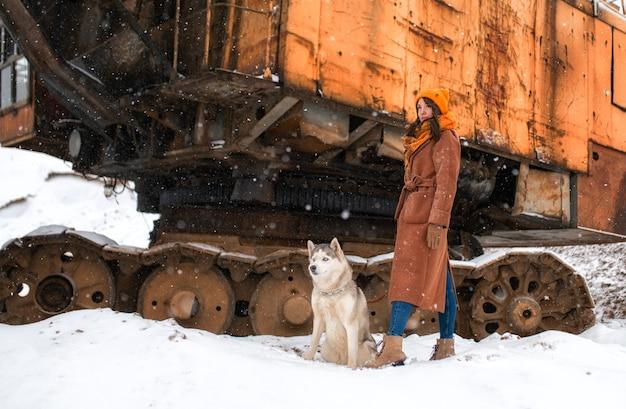 Dziewczyna w brązowym płaszczu, a obok siedzi pies husky