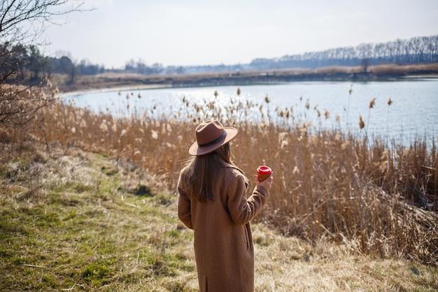 Dziewczyna w brązowym płaszczu, kapeluszu i okularach spaceruje po parku z jeziorem pod jasnym słońcem. picie herbaty z papierowego kubka. początek wiosny